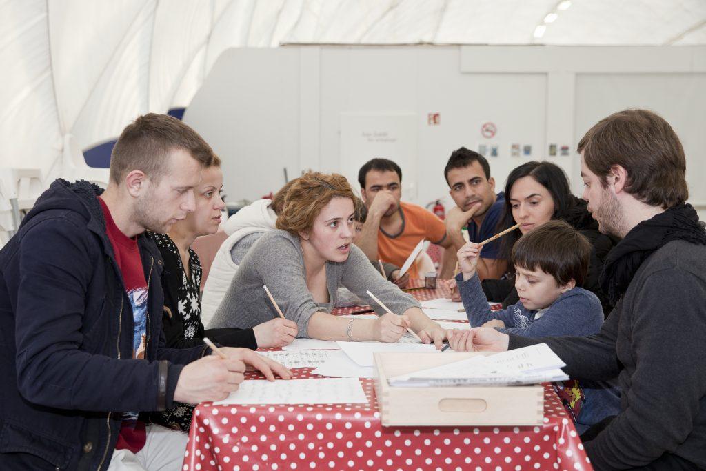 Der ehrenamtliche Deutschlehrer Max gibt Deutschunterricht in der Notunterkunft Traglufthalle © Kathrin Harms & Esteve Franquesa