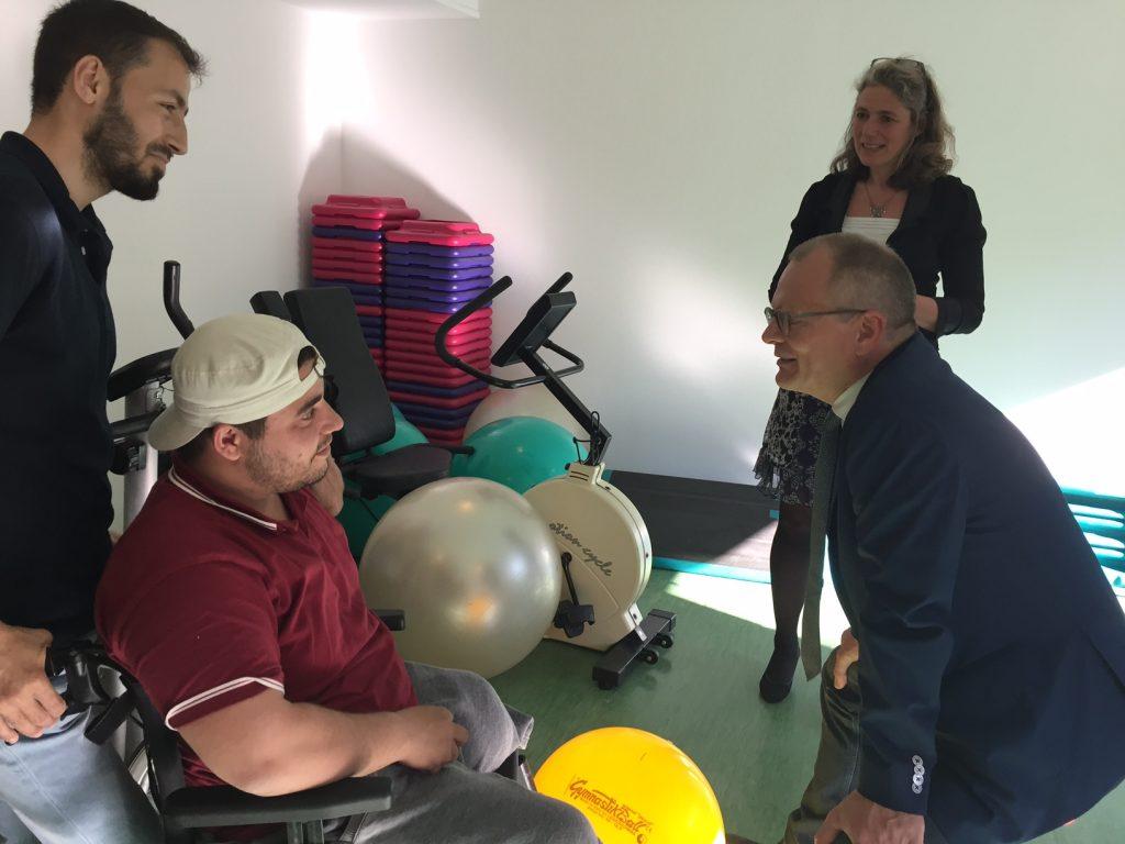 Präsident der Diakonie Ulrich Lilie unterhält sich mit Mohammed, der im Rollstuhl sitzt.