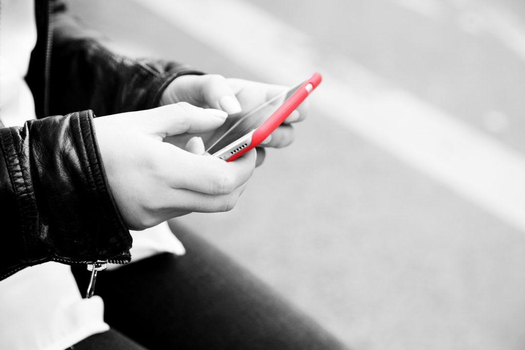 Frau tippt Nachricht an Mobiltelefon