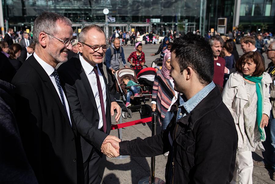 Zwei Männer geben sich die Hände. Ein Mann steht daneben und lächelt