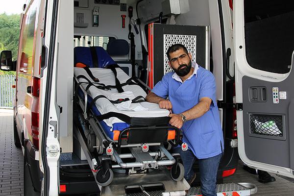 Ein Mann steht neben einer Liege an einem Krankentransporter