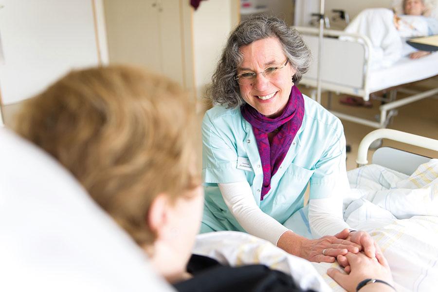 Frau hält Patientin im Bett die Hand