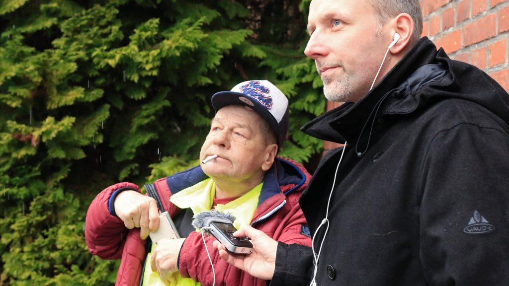 Zwei Männer, der recht Mann nimmt den anderen Mann mit einem Hörfunkgerät auf.