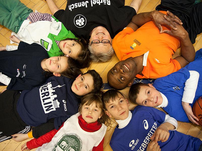 Kinder und Erwachsene liegen zusammen Kopf an Kopf in einem Kreis in einer Turnhalle