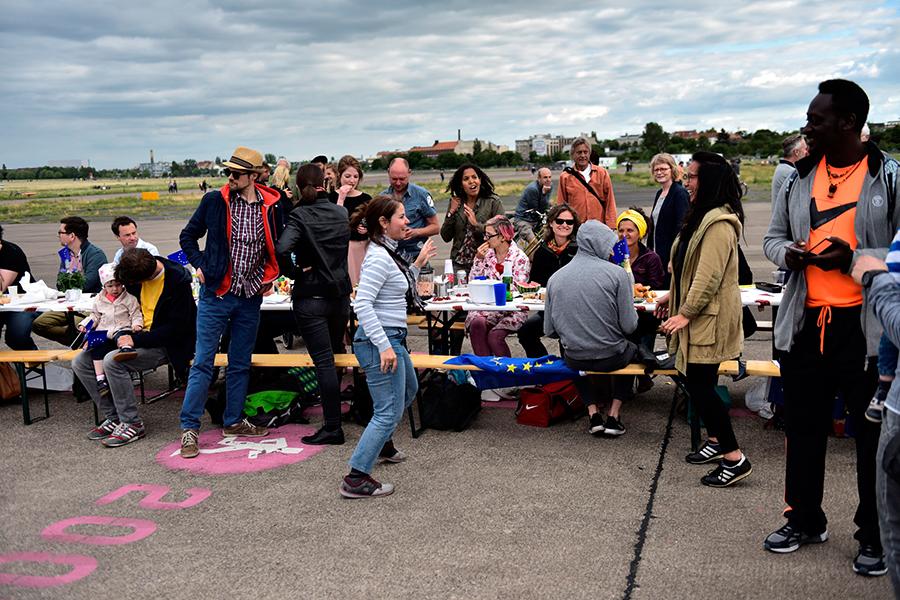 Menschen um eine Tafel auf dem Tempelhofer Feld
