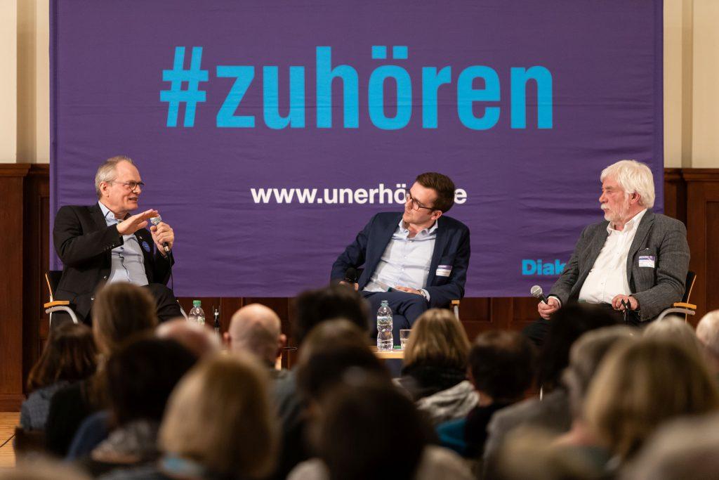 Drei Männer diskutieren vor Publikum