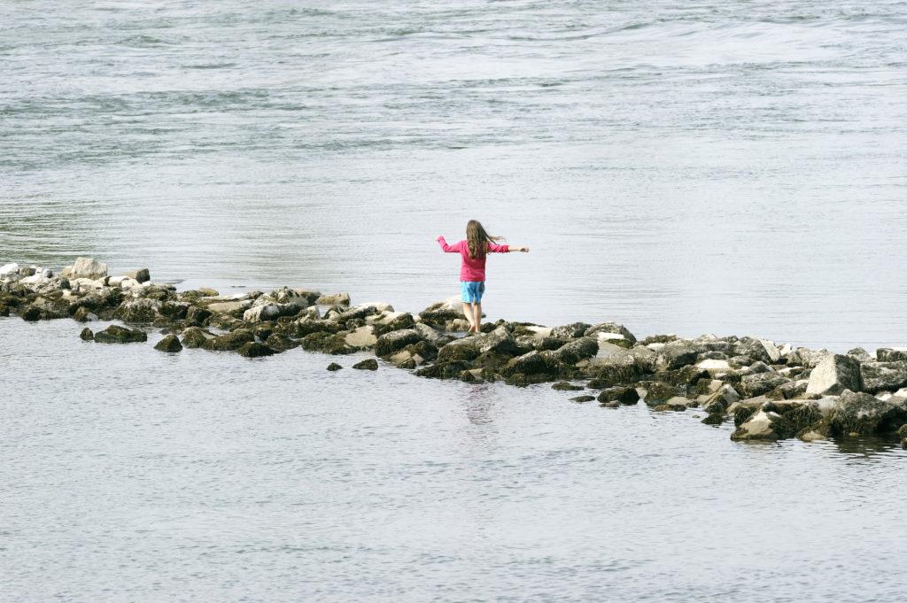 Kind balanciert auf einer Steinmauer im Rhein